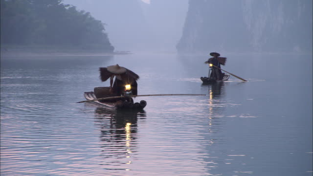 two men hold long poles as they stand in their slender boats on the li river. - lantern stock videos & royalty-free footage