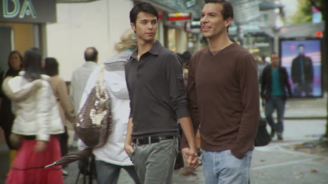 ms pan two men holding hands and walking on street / vancouver, british columbia, canada - native american ethnicity stock videos and b-roll footage