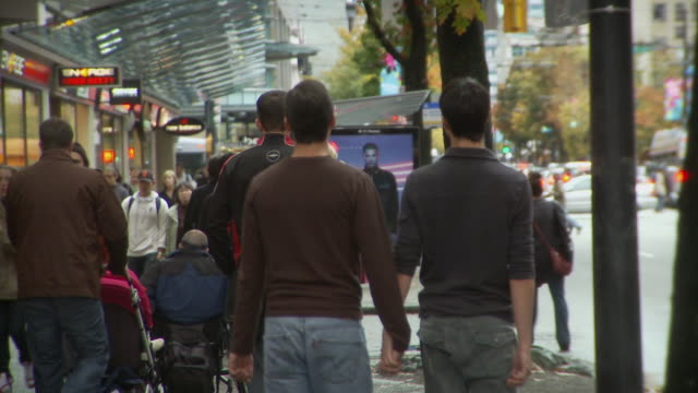 MS Two men holding hands and walking on street / Vancouver, British Columbia, Canada