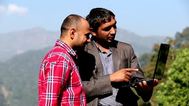 vidéos et rushes de hd: deux hommes tenant un ordinateur portable - vidéo portrait