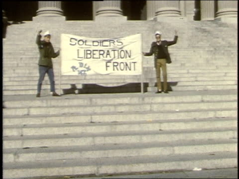 two men holding soldiers liberation front banner on steps of federal building / washington, d.c., united states - vietnam war stock videos & royalty-free footage