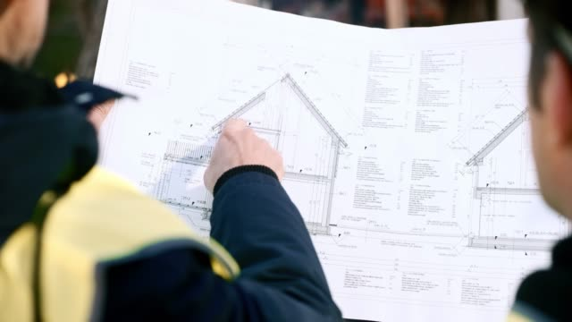 two men holding up the plan for a house and talking about it - architetto video stock e b–roll