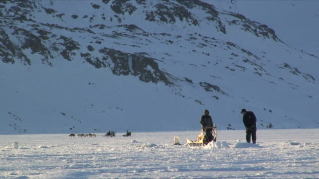 ws two men ice fishing, dog sledge and snow covered mountain in background, near tasiilaq, east greenland - greenland stock videos & royalty-free footage