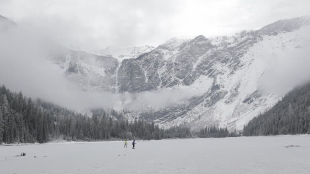 two men ice skating on a frozen mountain lake in glacier park, montana - glacier nationalpark stock-videos und b-roll-filmmaterial