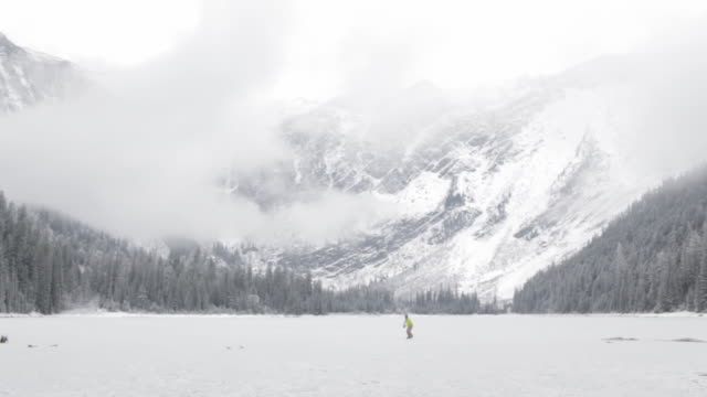 vídeos y material grabado en eventos de stock de two men ice skating on a frozen mountain lake in glacier park, montana - frío