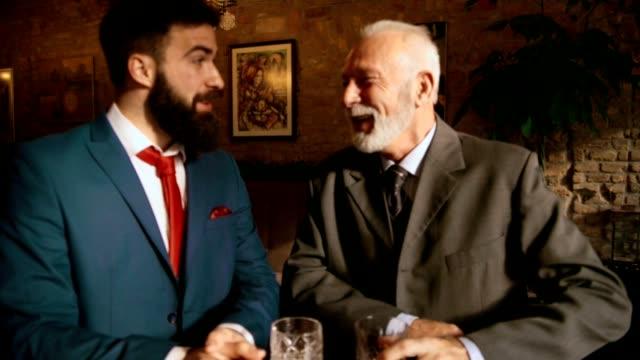 vidéos et rushes de deux hommes dans un bar - whisky
