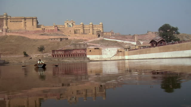 ws, two men in boat on maotha lake, amber fort in background, amber, rajasthan, india - rajasthan stock videos and b-roll footage