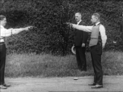 B/W 1922 two men in bullet-proof vests shooting pistols at each other outdoors / newsreel