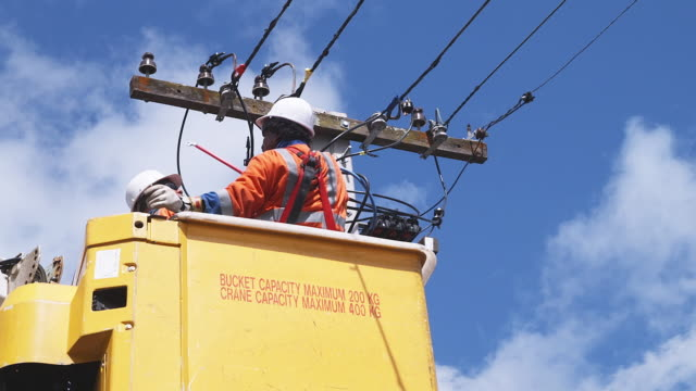 ms, la, two men in cherry picker working on overhead power line, auckland, new zealand - cherry picker stock videos & royalty-free footage