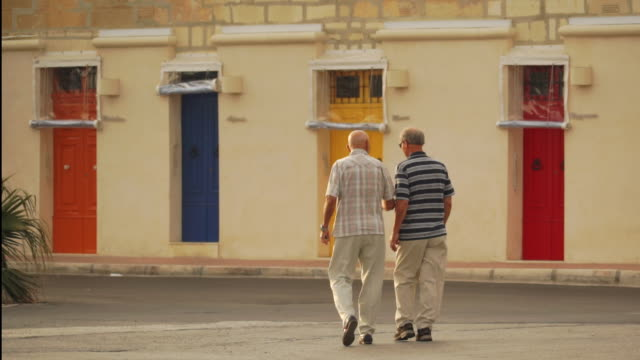 Two men in conversation walking, colorful doors background - Malta