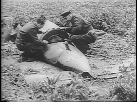 two men in england explore wreckage of unexploded flying unmanned german robot bomb / robot bomb in flight / bombs bursting on the ground / a flying... - 1944 stock videos & royalty-free footage