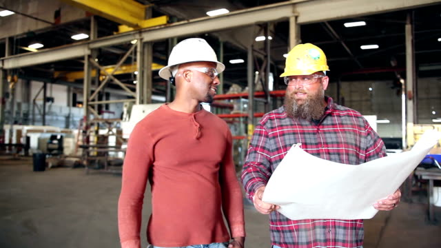 Two men in factory looking at floor plans