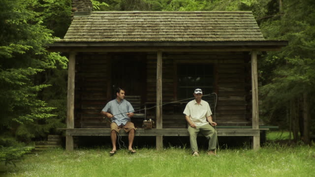 vidéos et rushes de ws two men in front rustic cabin in lush woods preparing fishing rods, morristown, vermont, usa - casquette de baseball