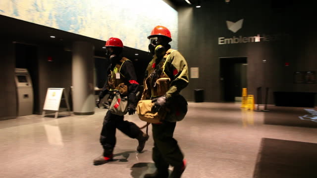 HANDHELD WIDE PAN two men in gas masks and hardhats join others in Barclays Center lobby - members of US Marines and FDNY take part in joint drill aimed at strenghting preparedness for chemical and biological attacks at Barclays Center