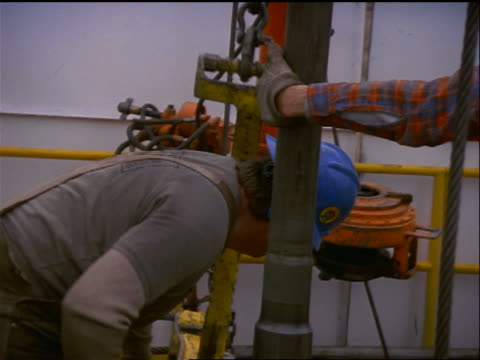 PAN two men in hard hats detaching clamp from pipe + moving pipe at oil/natural gas well / fire background