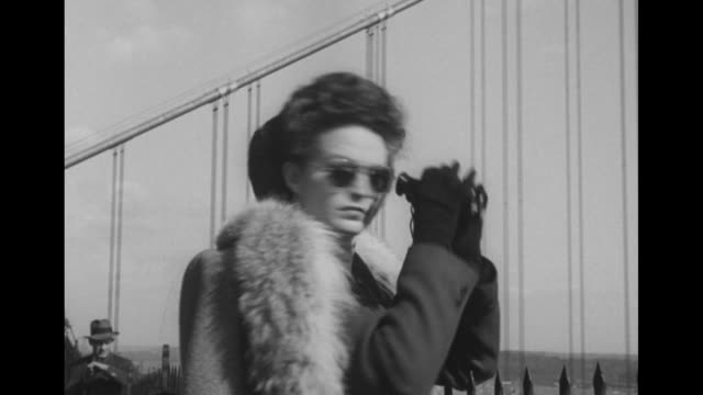 two men in hats and overcoats share a pair of binoculars / woman with fox fur and binoculars with spires of george washington bridge beyond / three... - canocchiale video stock e b–roll