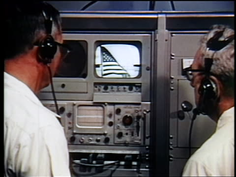 vídeos y material grabado en eventos de stock de view two men in headsets watching american flag on tv / first satellite broadcast - 1962