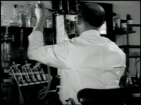 vídeos de stock, filmes e b-roll de two men in lab coats using microscopes researcher holding beaker tubing up to bubbling tube 'hospital of the rockefeller institute' sign dr homer f... - 1930