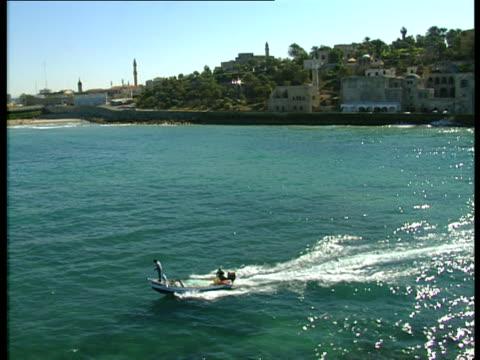 aerial ws pan two men in motorboat near old town of jaffa, dan metropolis, israel - jaffa stock videos & royalty-free footage