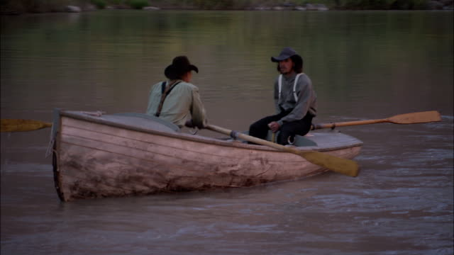 stockvideo's en b-roll-footage met two men in old-fashioned western clothing row a wooden boat down the colorado river. - men