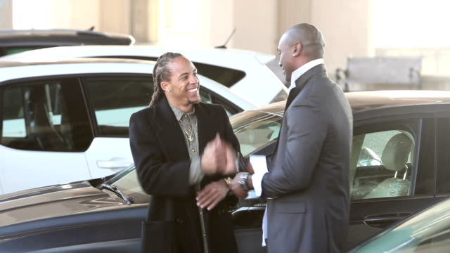Two men in parking lot talk, embrace and shake hands