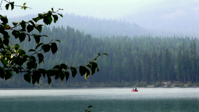 Two men in red fishing boat going across frame on misty mountain lake.