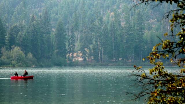 vídeos y material grabado en eventos de stock de two men in red fishing boat going across frame on misty mountain lake. - montana