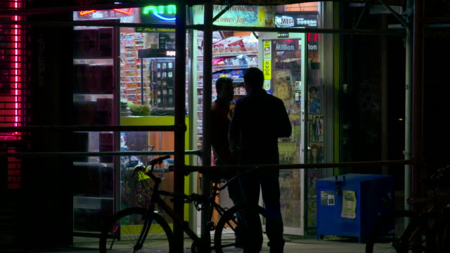 vídeos de stock, filmes e b-roll de two men in shadow stand in a doorway of a convenience store at night talking and smoking - loja de conveniência