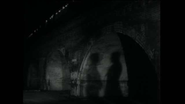 two men in silhouette talking in shadows under bridge; 1955 - silhouette stock videos & royalty-free footage