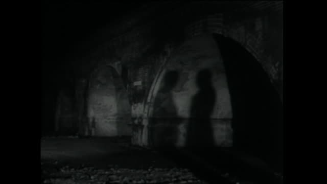 two men in silhouette talking in shadows under bridge; 1955 - low stock videos & royalty-free footage
