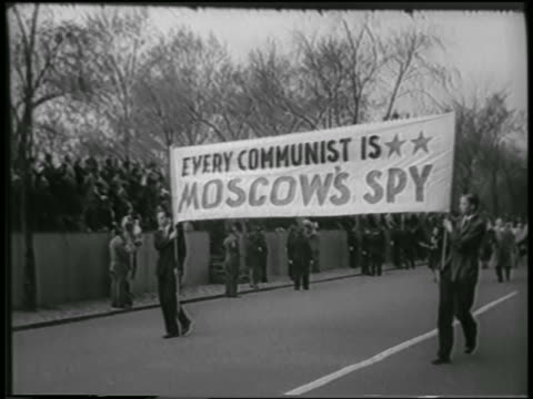 "vídeos de stock, filmes e b-roll de two men in suits carrying ""every communist is moscow's spy"" banner in demonstration - 1951"