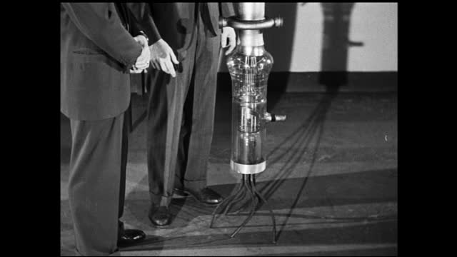 vídeos de stock e filmes b-roll de two men in suits examining and talking about rocket like structure with light bulb on the top; their shadows are casted on the wall - 1940 1949