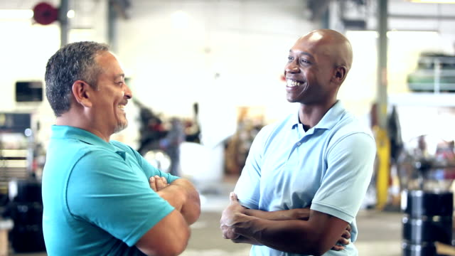 Two men in truck repair shop talking