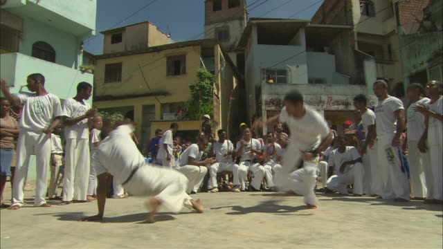 ms two men in white perform capoeira as several onlookers in white clap and cheer them on/ brazil - brazilian culture stock videos & royalty-free footage