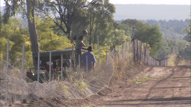 WS Two men inserting fence posts along dirt road, Dingo Fence, Queensland, Australia