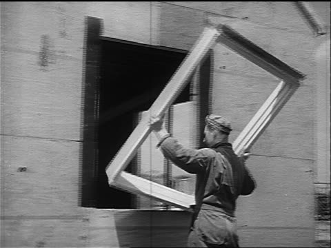 b/w 1947 pan two men installing window frame in house under construction - 1947 stock videos & royalty-free footage