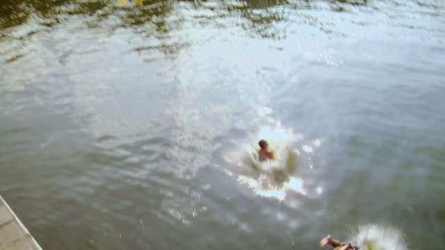 slo mo ha ms td ws two men jumping off boat deck into lake / potsdam, germany - badbyxor bildbanksvideor och videomaterial från bakom kulisserna