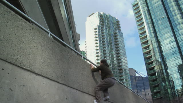 Ms La Two Men Jumping Up And Over Building Ledge Performing Parkour Vancouver British Columbia Canada Stock Footage Video