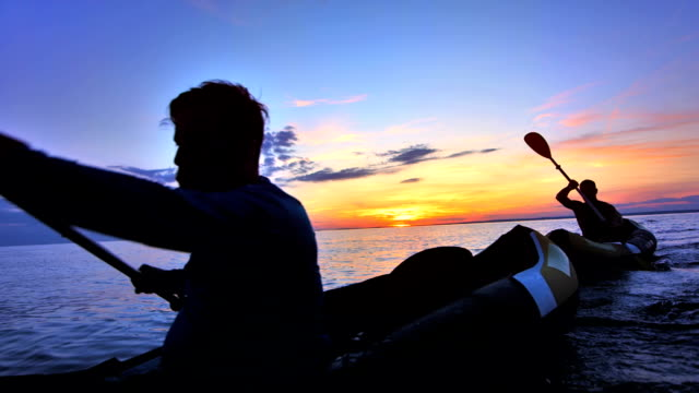 slo mo two men kayaking at sunset - canoe stock videos & royalty-free footage