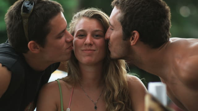 two men kissing the same girl as she looks at the camera - female with group of males stock videos & royalty-free footage