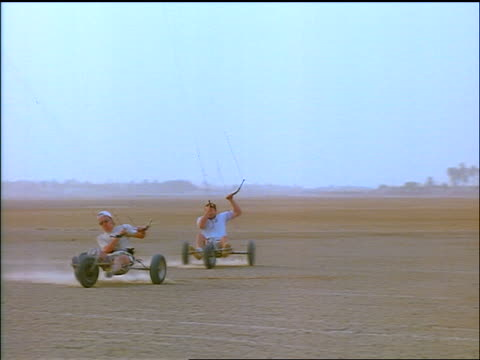 pan two men kite sailing spin 180 degrees + travel backwards on rocky desert / senegal, africa - kite sailing stock videos and b-roll footage