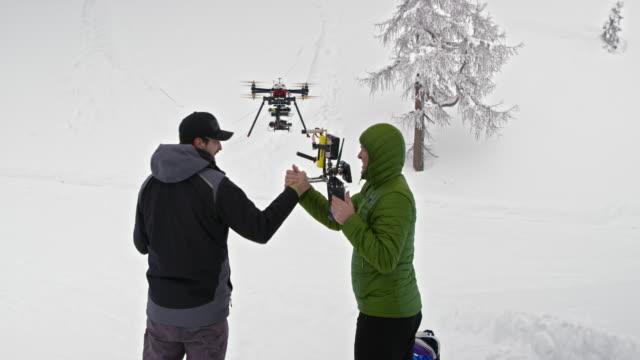 vídeos y material grabado en eventos de stock de dos hombres de un abejón del aterrizaje en la nieve y haciendo alto cinco - chaqueta de esquiar