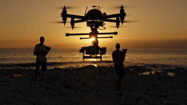two men landing a drone on beach at sunset - in silhouette stock videos & royalty-free footage