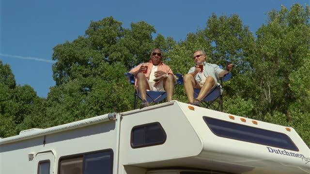 MS LA Two men laughing as they sit on deck chairs on roof of parked motor home / Asheville, North Carolina, USA