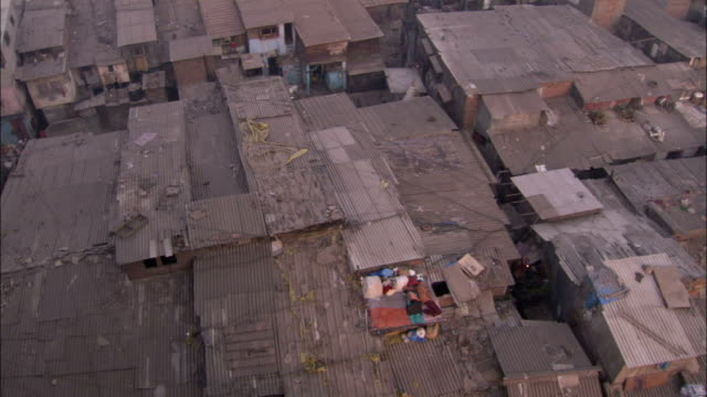 two men lie in sleeping bags on a shantytown rooftop in the dharavi slum in mumbai india. available in hd. - 寝袋点の映像素材/bロール