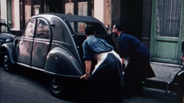two men lift a car to move it into a parking space in paris, france. - 1950 stock-videos und b-roll-filmmaterial