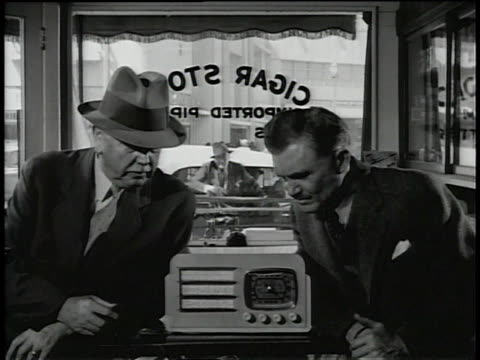 1945 Two men listening to a radio when a man throws an object through the window