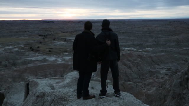 two men look out over badlands national park - badlands national park video stock e b–roll
