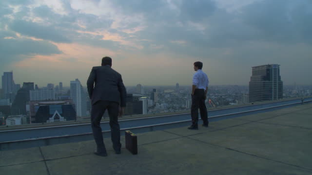 ws pan two men looking around on rooftop  / bangkok, bangkok, thailand - kompletter anzug stock-videos und b-roll-filmmaterial
