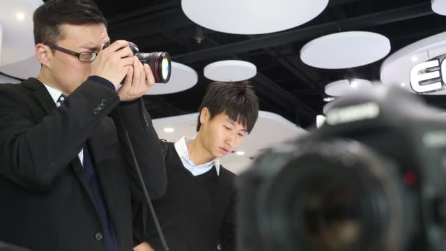 two men looking at canon dslr cameras in showroom canon showroom in hong kong on january 29, 2013 in hong kong, hong kong - digital spegelreflexkamera bildbanksvideor och videomaterial från bakom kulisserna